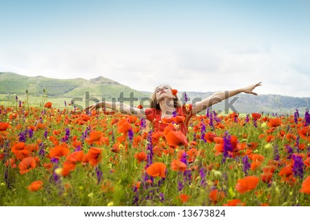 girl spreading her arms in the middle of a poppy field with blue cloudy sky, 'outdoor freedom' - stock photo