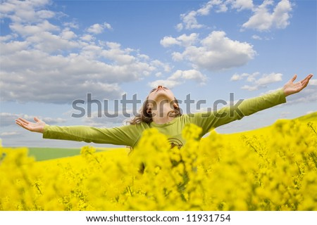 girl spreading her arms in the middle of a rapeseed field with blue cloudy sky, 'outdoor freedom' - stock photo