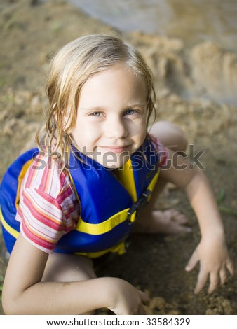 girl squatting on beach with life jacket on - stock photo