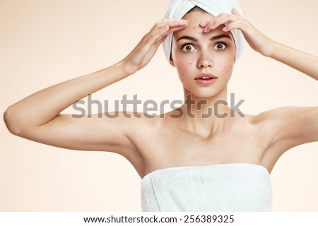 Girl squeezing her pimples, removing pimple from her face.  Woman skin care concept / photos of ugly problem skin brunette girl on beige background  - stock photo