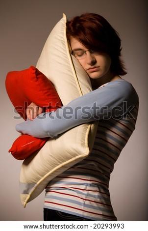 Girl stand, sleep and hugs pillows - stock photo