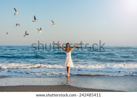 Girl standing at the beach during beautiful sunset. - stock photo