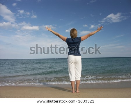 Girl standing at the beach expressing joy of life - stock photo