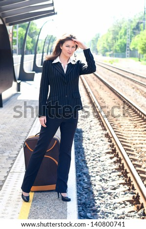 girl standing at the bus stop and waiting for the train