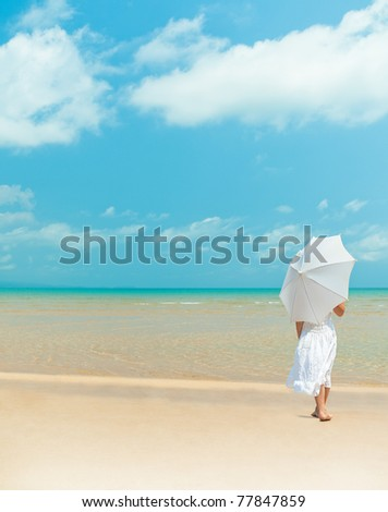 girl standing back on the beach  in white dress with umbrella - stock photo