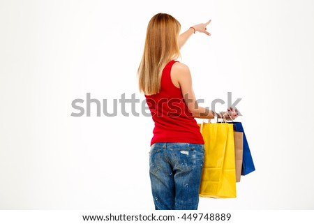 Girl standing back to camera with purchases over white background. - stock photo