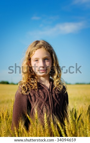 girl standing in a wheat field with a bright blue sky
