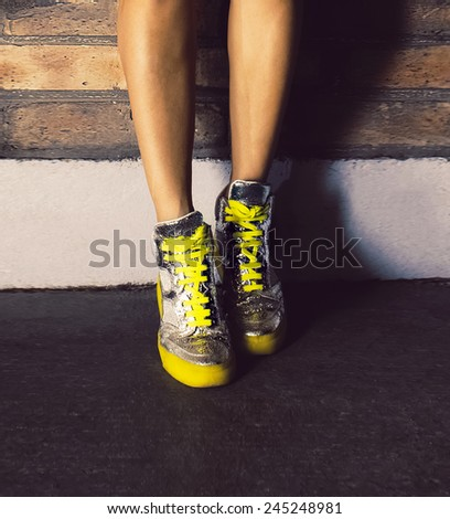 Girl standing in fashionable sneakers brick wall. Urban fashion style - stock photo