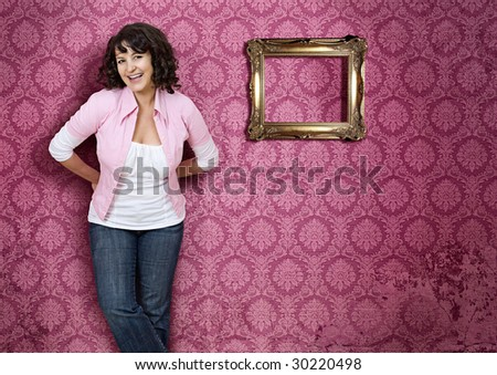 girl standing in front of a pink wallpaper - stock photo