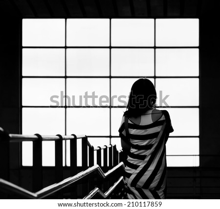 girl standing in front of the window - stock photo