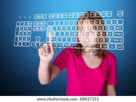 Girl standing in front of virtual screen, pressing enter key on keyboard - stock photo