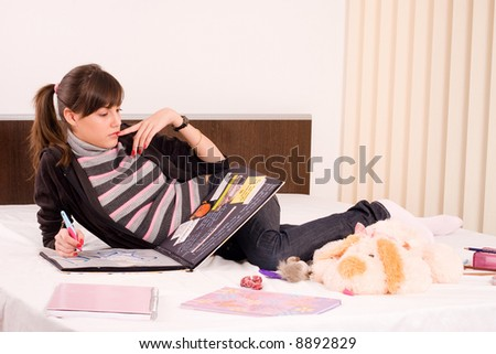 girl standing in her bed with her notebooks and fluffy toy