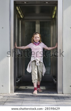 Girl standing in open elevator - stock photo