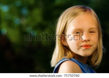 Girl standing in sunshine with trees as background - stock photo