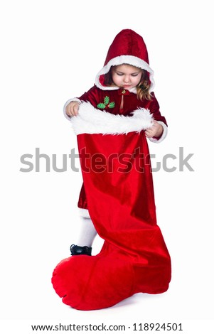 Girl standing in the costume of a Santa Claus and holding in her hand a big red boots
