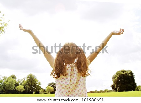 Girl standing in the park with her arms outstretched towards the sky. - stock photo