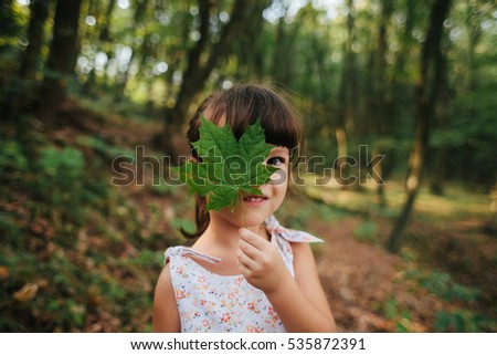 girl standing in the woods holding a leaf in his hands. hidden behind leaf