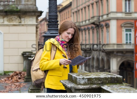 girl standing near parapet and looking to the map at the Bologna street