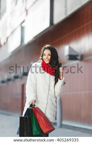 Girl standing near shopping mall, looking aside and smiling. Beautiful girl holding colorful shopping bags in one hand and holding another hand near hair. Wearing white coat and red scarf. Outdoor - stock photo