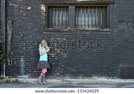 Girl standing next to brick wall smelling flowers - stock photo