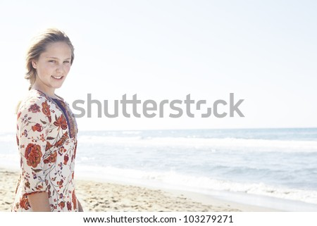 Girl standing on a beach shore, smiling at the camera. - stock photo
