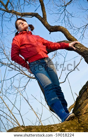 girl standing on a dry tree, and looks forward - stock photo