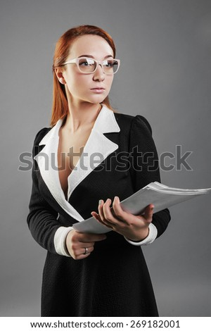 Girl standing on a gray background in the hands of paper, black dress, glasses, business style,
