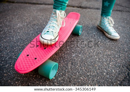 Girl standing on a pink skateboard outdoors on asphalt