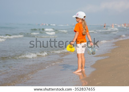 girl standing on a sandy beach with bucket and slaps hands and looks into the distance