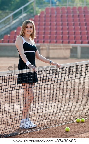 Girl standing on a tennis court for lessons with net. - stock photo