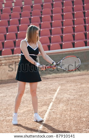 Girl standing on a tennis court for lessons with raquet. - stock photo