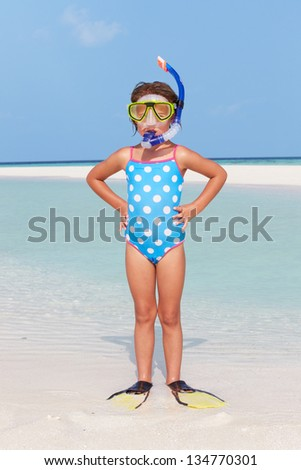 Girl Standing On Beach Wearing Snorkel And Flippers - stock photo