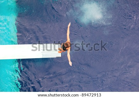 Girl standing on diving board, preparing to dive - stock photo
