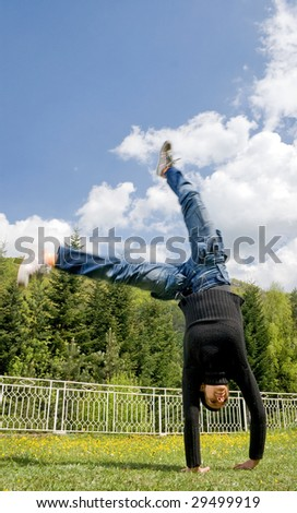 girl standing on hands in a green meadow - stock photo