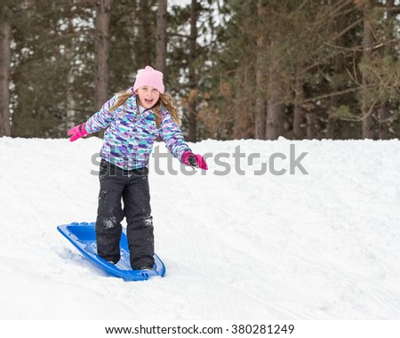 Girl standing on her sled while sledding down a hill.  Snow surfing and looking at camera.  Copy space in right part of frame.