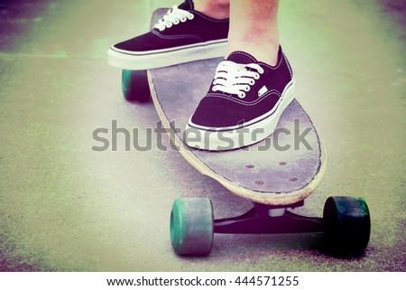 Girl standing on long board skateboard - stock photo