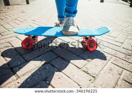 GIrl standing on skateboard on the street - stock photo