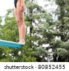 Girl standing on springboard, preparing to dive. - stock photo