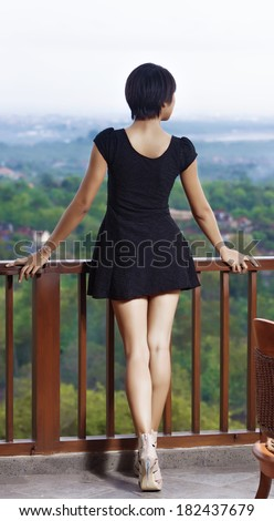 girl standing on the balcony, leaning his hands on the railing. dressed in black short dress. open legs, high heels.  against the backdrop of the island and the bay - stock photo