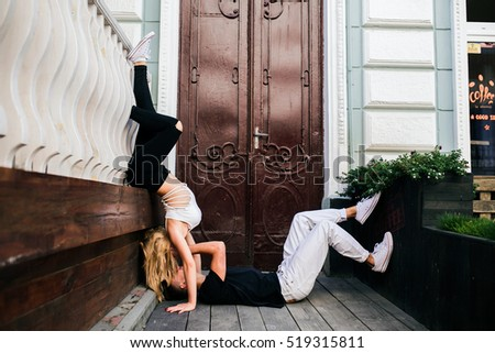 girl standing on the hands, a guy lying on the ground on a background of doors
