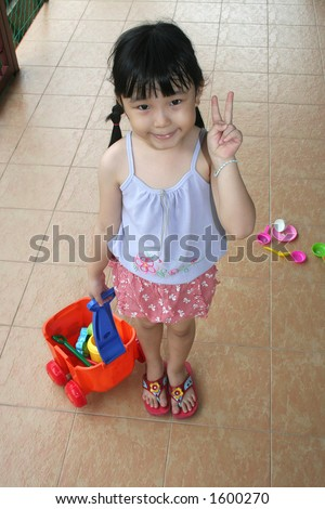 Girl standing & pulling beach playset - stock photo
