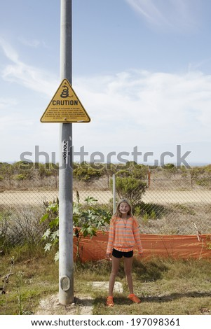 Girl standing under snake warning sign, California, USA - stock photo