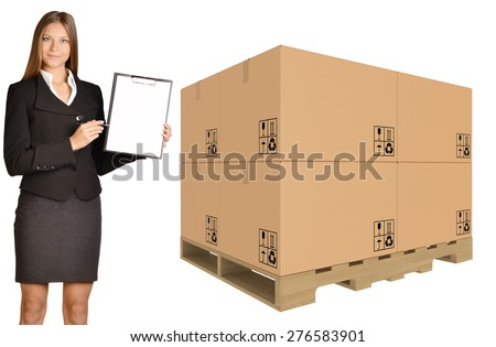 Girl standing with cardboard boxes on pallet and showing in clipboard. - stock photo