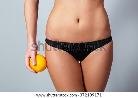 Girl stands and holding orange isolated on grey