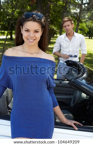 Girl stands leaning on cabriolet door, guy stands behind car, focus on girl