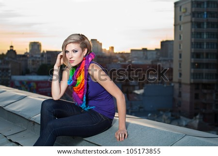 girl stands on the roof on the background of a big city and the blue sky - stock photo