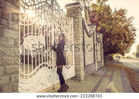 Girl staying in front of big white gates