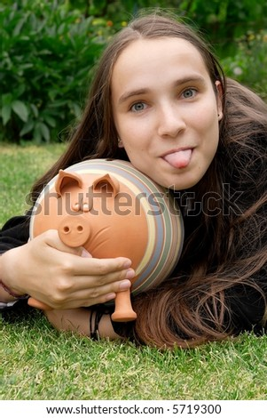 Girl sticking her tongue out with piggy bank in her hands - stock photo