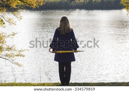 Girl stood alone next to a lake in the park, autumn, water, beautiful, season - stock photo