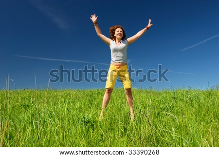Girl stratching hands on the field under sun